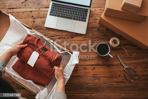 Women, owener of small business packing product in boxes, preparing it for delivery