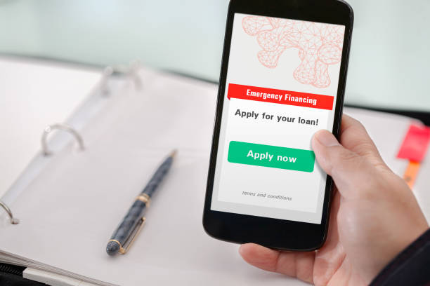 Small business owner applying for emergency financing using a mobile phone. stock photo