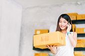 中小企業経営者、アジアの女性は、自宅オフィスで仕事発注書を受信する携帯電話の呼び出しを使用してパッケージ ボックスを保持します。オンライン マーケティングの配信、スタートアップ中小企業起業家やフリーランスのコンセプト