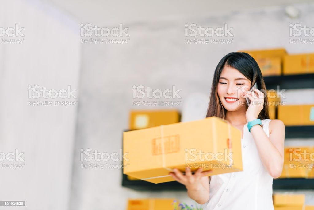 Small business owner, Asian woman hold package box, using mobile phone call receiving purchase order, working at home office. Online marketing delivery, startup SME entrepreneur or freelance concept stock photo