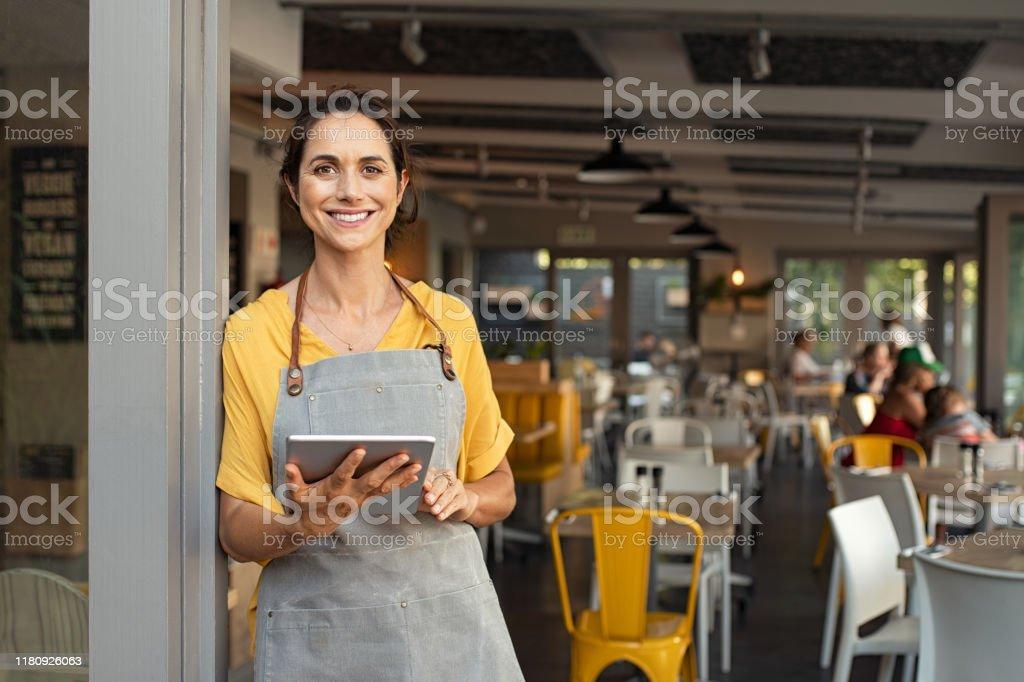 Propietario de una pequeña empresa en la entrada mirando la cámara - Foto de stock de 40-49 años libre de derechos