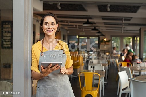 istock Small business owner at entrance looking at camera 1180926063