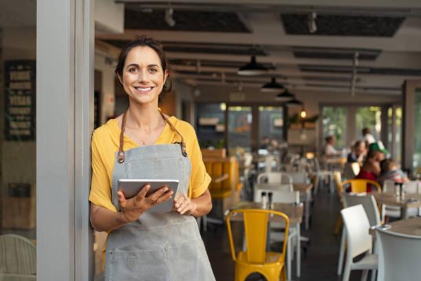 小企業主在入口處看著相機 - 女性 個照片及圖片檔