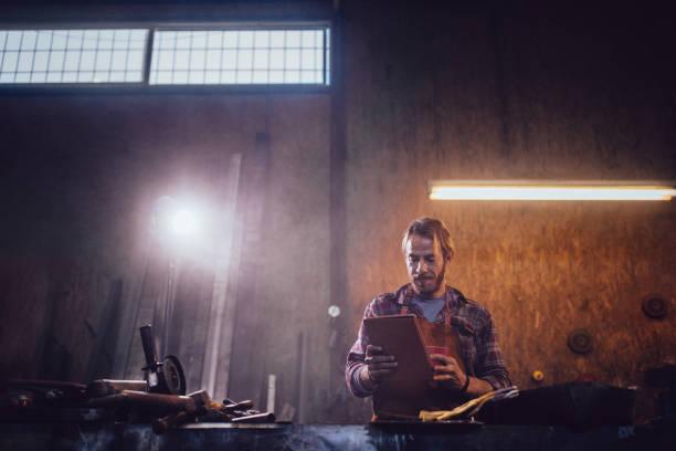 kleine unternehmen eigentümer handwerker mit tablet und online-recherche - tattoo maker online stock-fotos und bilder