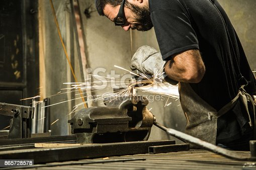 istock Small business owner grinding at his garage 865728578