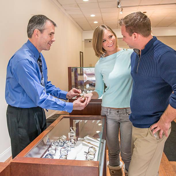 kleinunternehmen eigentümer helfen glückliche paar einkaufen für schmuck - diamanten kaufen stock-fotos und bilder