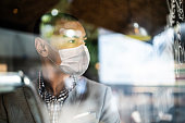 Small business owner looking out of window with face mask