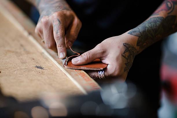 small business owner making leather products in his shop - leder portemonnaie herren stock-fotos und bilder