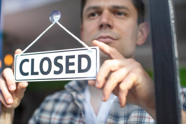 Small Business Owner With Serious Expression Putting Up Closed Sign During Recession Or Health Pandemic – Foto