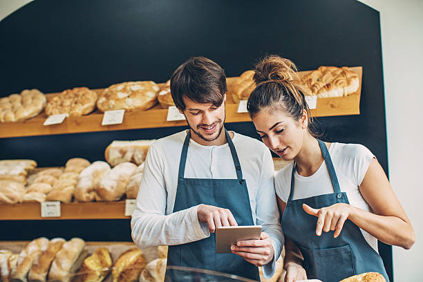 Small business owners checking a digital tablet Couple of young bakers in their bread shop looking at digital tablet. female sandwich stock pictures, royalty-free photos & images