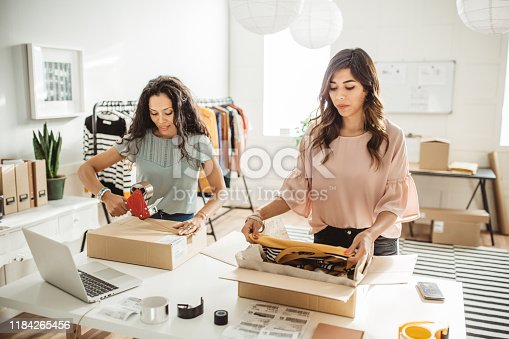Working women at their store. They wearing casual clothing and accepting new orders online