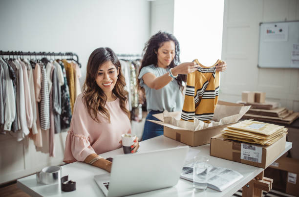 Small business owners Working women at their store. They wearing casual clothing, accepting new orders online and packing merchandise for customer clothes in box stock pictures, royalty-free photos & images