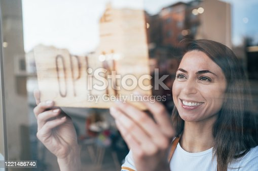 Portrait of a happy business owner hanging an open sign on the door at a cafe and smiling