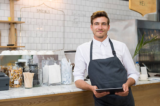 Small business Successful small business owner holding digital tablet and looking at camera. Happy smiling waiter with apron and digital tablet leaning on counter. Portrait of young entrepreneur of coffee shop posing. waiter stock pictures, royalty-free photos & images
