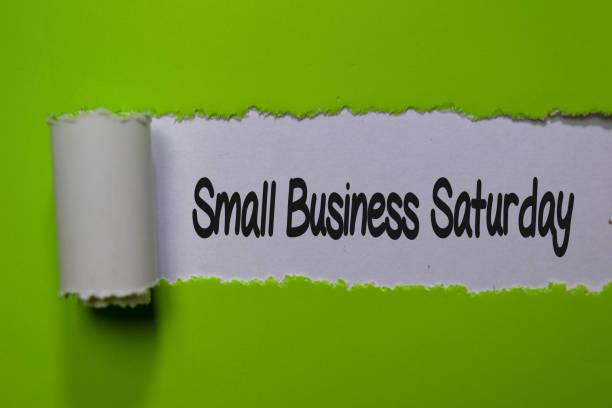 小型企業星期六寫在白色和綠色撕裂的紙張上 - small business saturday 個照片及圖片檔