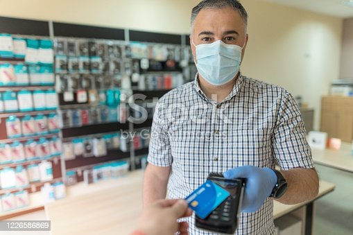 Small business restarting work amid Coronavirus pandemic, receiving mobile payment from a customer
