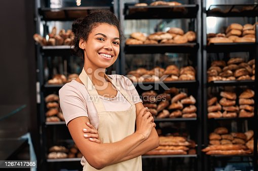 istock Small Business. Young woman in apron at bakery shop crossed arms posing to camera cheerful 1267417365