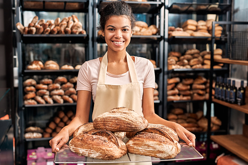 Young woman wearing apron assistant at friendly bakery shop small business holding rye bread loafs posing to camera smiling happy