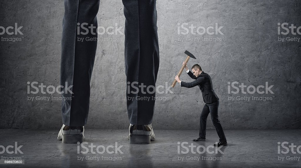 Small businessman hitting giant legs of another with hammer stock photo