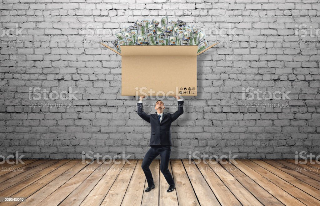 Small businessman holding large carton box full of USD bills stock photo