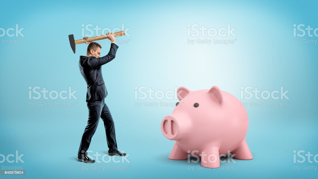 A small businessman holds a heavy hammer over his head to break a large piggy bank stock photo