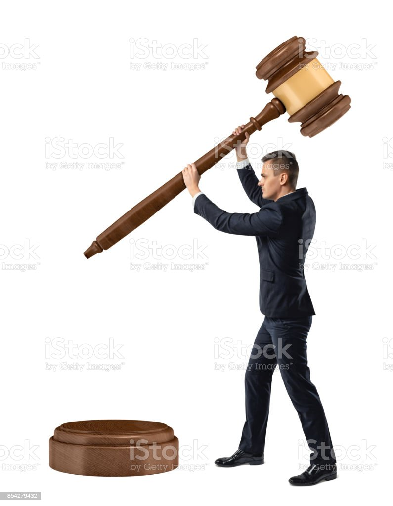 A small businessman on isolated white background holds and lowers a giant judge gavel on a sound block. stock photo