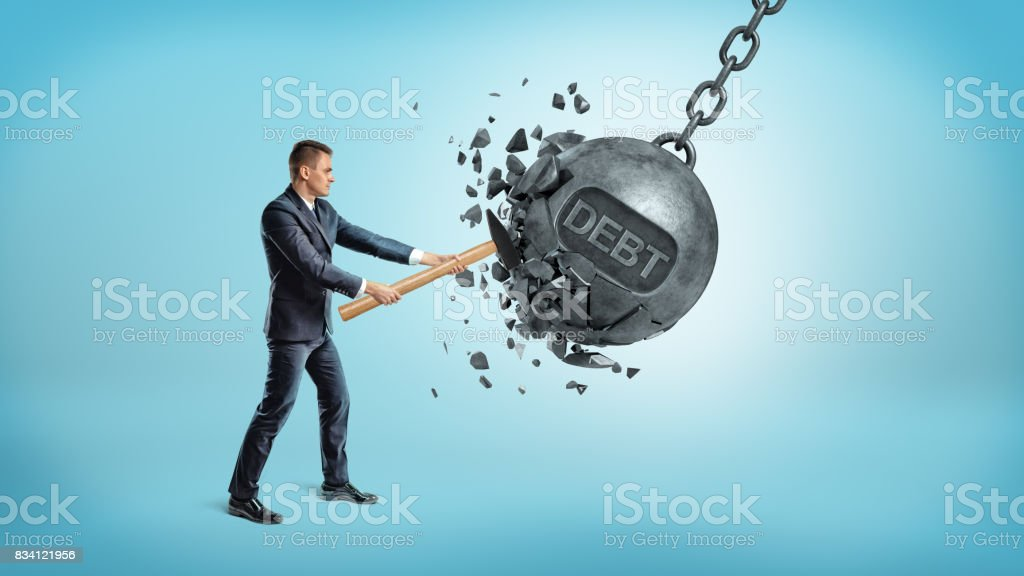 A small businessman smashes a giant swinging iron ball with a word DEBT on it using a hammer - Foto stock royalty-free di Adulto