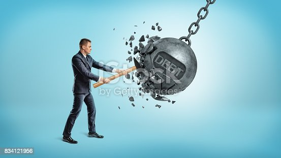 istock A small businessman smashes a giant swinging iron ball with a word DEBT on it using a hammer 834121956