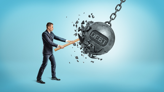A Small Businessman Smashes A Giant Swinging Iron Ball With A Word Debt On It Using A Hammer - Fotografie stock e altre immagini di Adulto