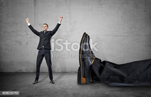 istock Small businessman standing with his arms up near giant leg 628220752