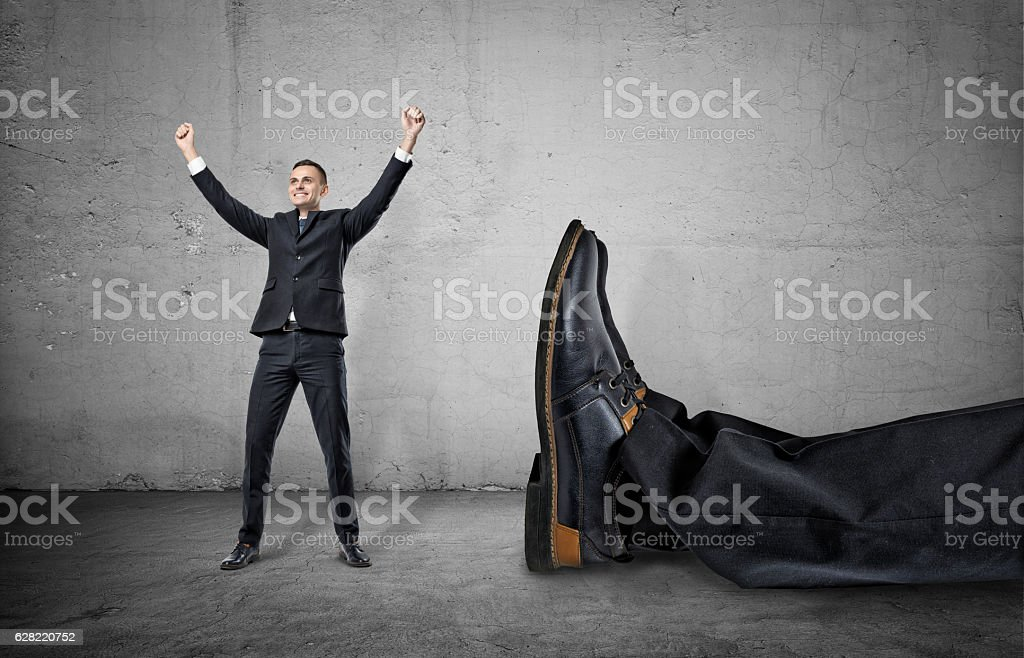 Small businessman standing with his arms up near giant leg – Foto