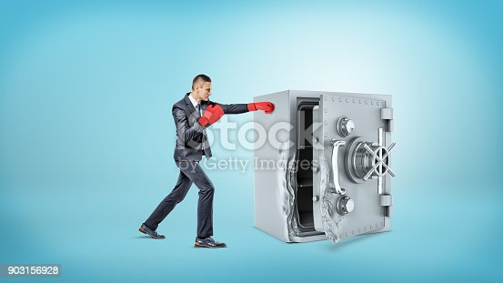 160558362 istock photo A small businessman wears red boxing gloves and hits a large broken metal safe 903156928