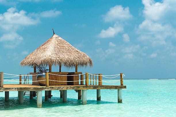 A small cabana on a dock over clear water in the sun stock photo