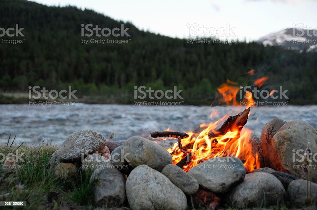 small campfire between rocks stock photo
