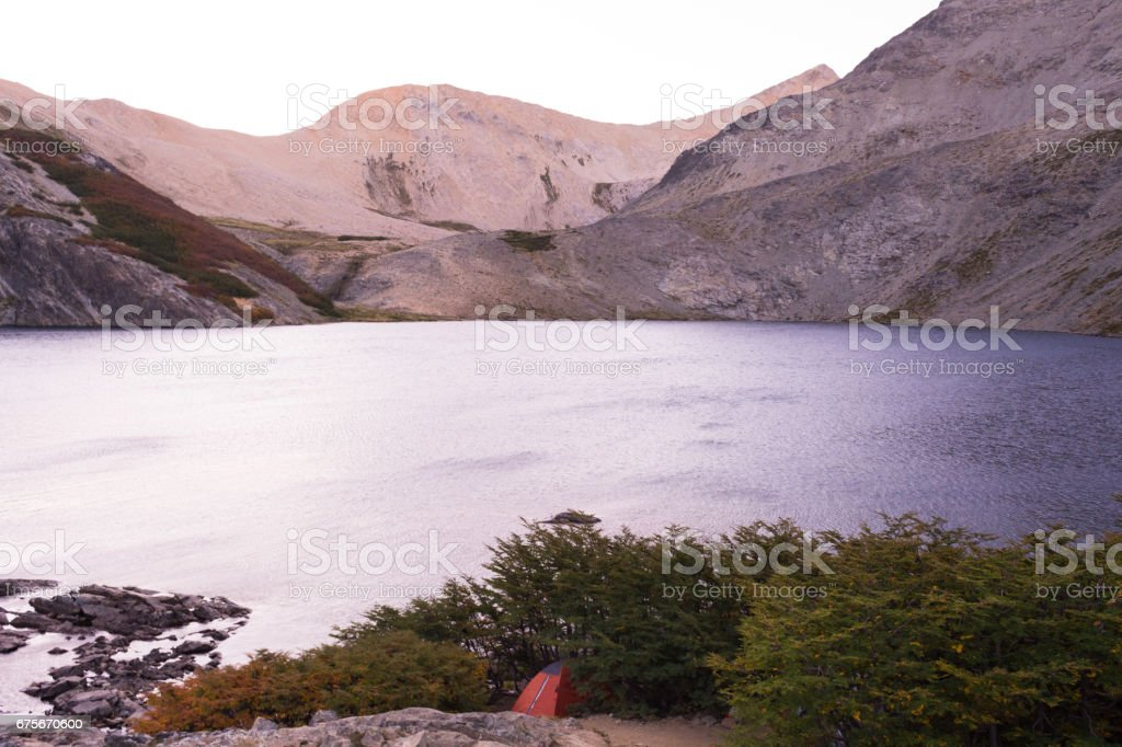 Small camping orange tent alone in a campsite near a lagoon royalty-free stock photo