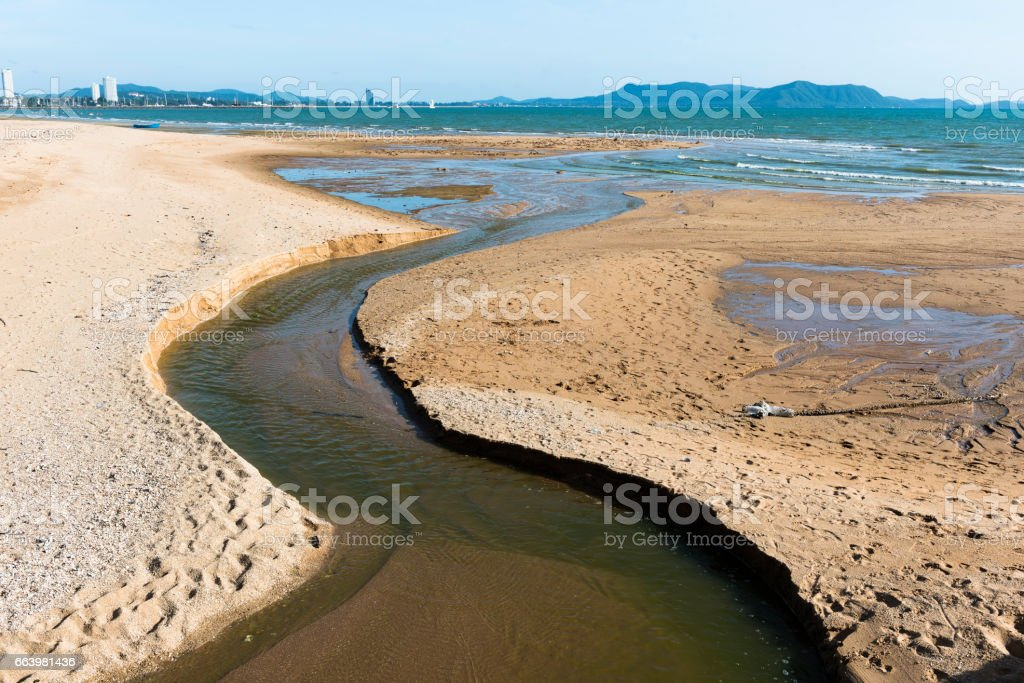 Small canal on sand beach bring water to the sea stock photo