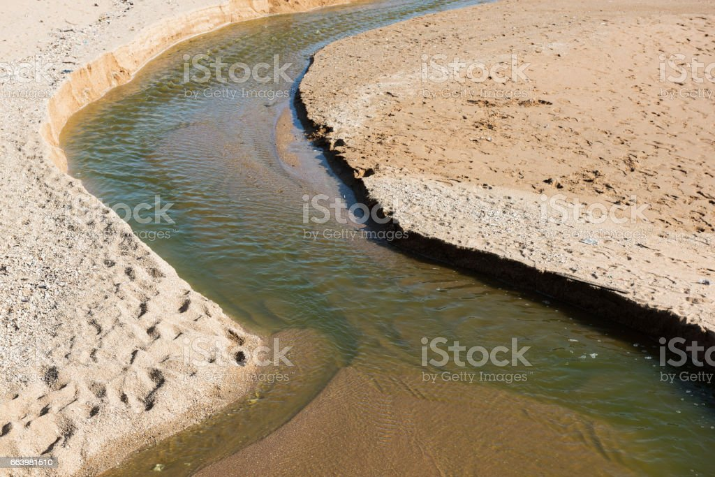 Small canal on sand beach stock photo