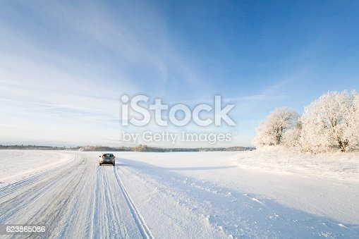 istock Small car driving along a snowy, icy road in winter 623865086