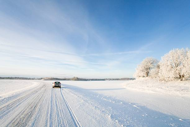 Small car driving along a snowy, icy road in winter – Foto