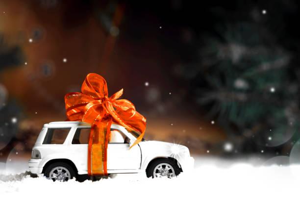 kleinwagen mit einer dekorativen schleife im schnee - autoschleifen stock-fotos und bilder