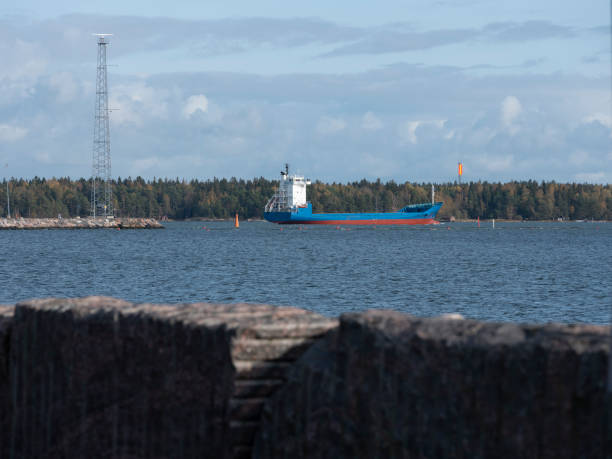 A small cargo ship sailing in front of the commercial port. stock photo
