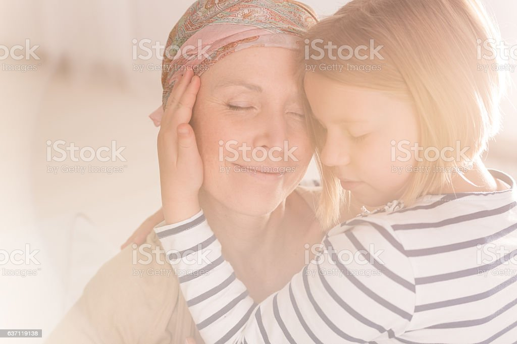 Small caring child embracing mother stock photo