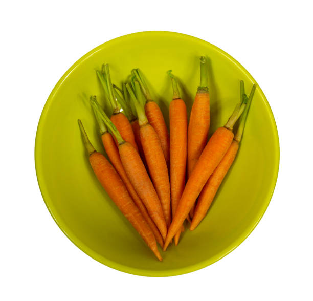 small carrots on a plate isolated on white background stock photo