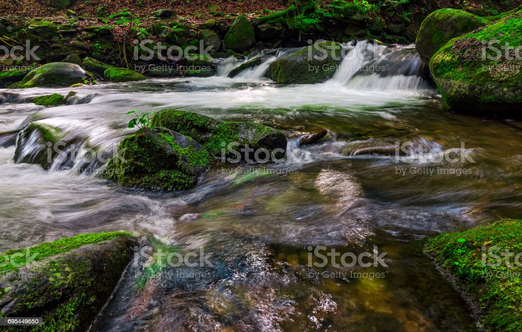 small cascade on the stream among bouders stock photo