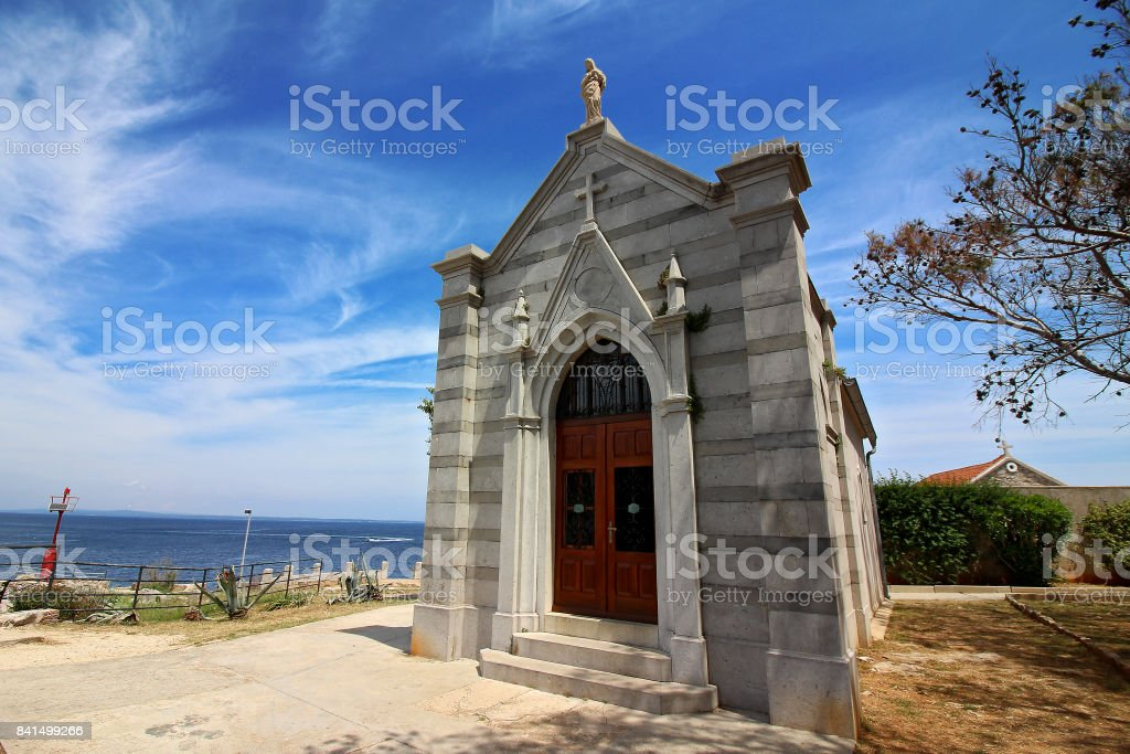 Small catholic church near sea in a fishing village on a hot summer day stock photo