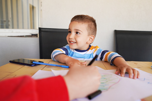 818512928 istock photo Small caucasian boy little kid woman and son mother and child sitting by the table on the balcony or terrace drawing with color pencils on the paper using crayons in the learning process of growing up 1221925185