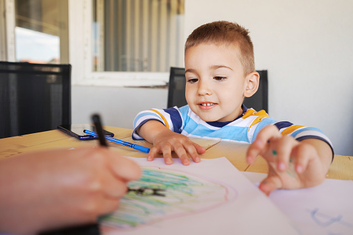818512928 istock photo Small caucasian boy little kid woman and son mother and child sitting by the table on the balcony or terrace drawing with color pencils on the paper using crayons in the learning process of growing up 1221925191
