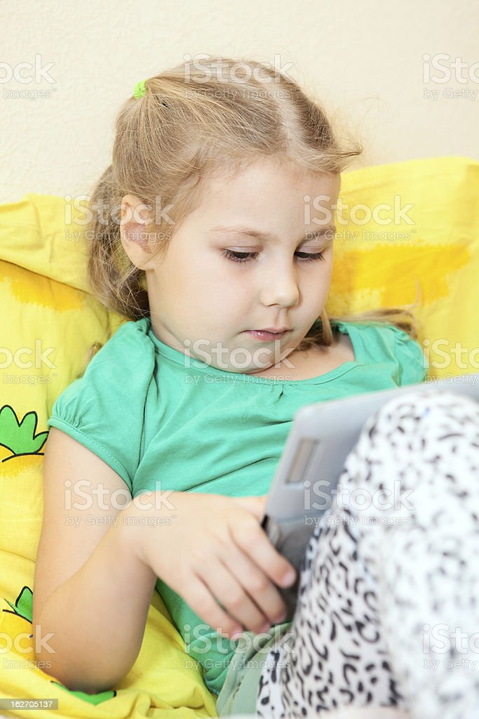 Small Caucasian child with digital tablet pc in bed royalty-free stock photo