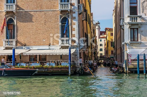 Venice/Italy - August 22, 2018: A small channel of Venice called Rio de L'Alboro with a forged bridge over it and many gondoliers