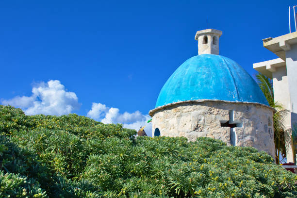 Small chapel surrounded by a beautiful green bush. Sunny day with blue sky and white clouds. Cozumel southern tip stock photo